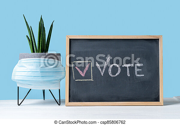 Vote Written On Blackboard. The concept of making choices with medical mask. Presidential and parliamentary elections. Calling for voting, democracy - csp85806762