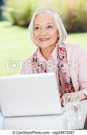 vrouw, portiek, weg, bejaarden, het kijken, terwijl, gebruik, het glimlachen, draagbare computer - csp24872267