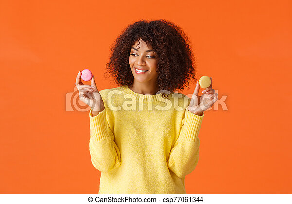 Waist-up portrait dreamy cute modern african-american female treat herself, eating desserts on cheat day, skip diet, holding two tasty macarons and smiling, like sweets, standing orange background - csp77061344