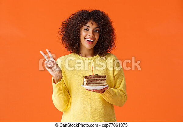 Waist-up portrait happy african-american woman in yellow sweater, showing peace sign and say cheese, birthday girl taking photo with b-day cake and candle, making wish, standing orange background - csp77061375