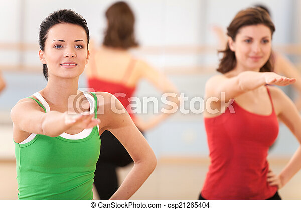 waist up portrait of instructor with fitness class. young girls performing step aerobics exercise in gym - csp21265404