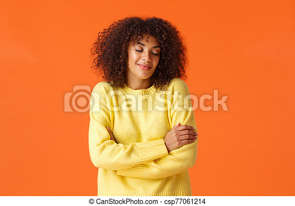 Waist-up portrait romantic lovely young woman dreaming about travelling somewhere warm on winter holidays, close eyes and smiling sensually, embracing own body, standing orange background - csp77061214