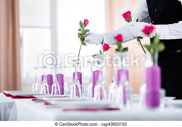 Close Up Of Waiter Arranging Roses In Vase On Wedding Table