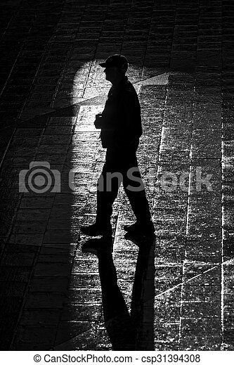 Walking man with long shadows in high contrast - csp31394308