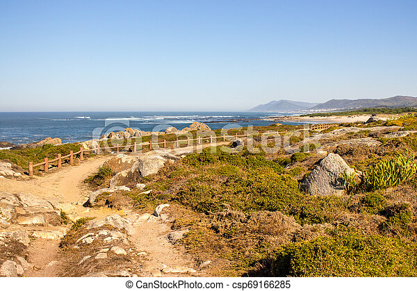 Walkway with fence along Atlantic Ocean coast with mountain on background. Portugal nature. Moss and grass on rocks at seaside. - csp69166285