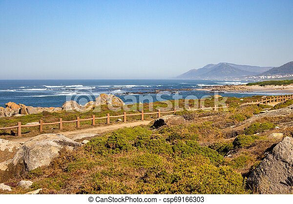 Walkway with fence along Atlantic Ocean coast with mountain on background. Portugal nature. Moss and grass on rocks at seaside. - csp69166303