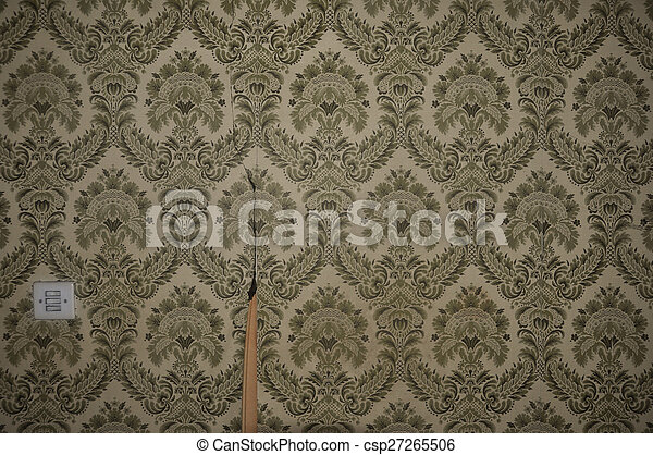 Vintage torn wallpaper pattern and light switch on abandoned house wall. abstract retro background.
