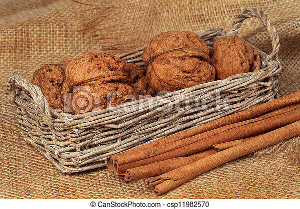 Walnuts in a wicker basket and cinnamon on sacking - csp11982570