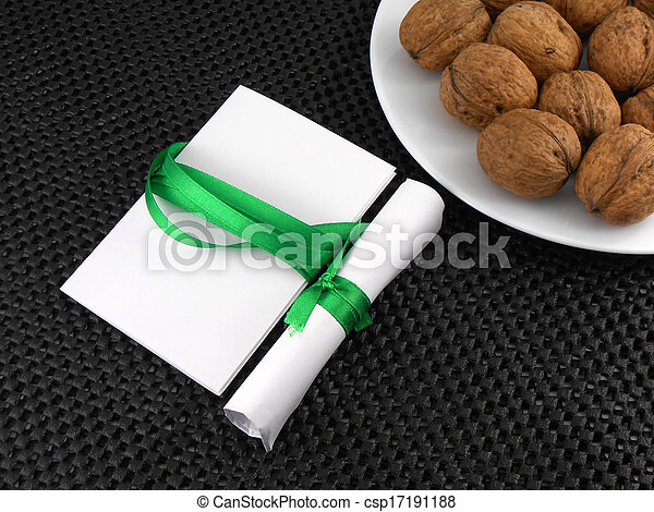 Walnuts on a white plate with invitation card - csp17191188