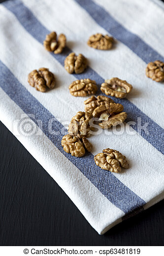 Walnuts on cloth over black background, side view. Close-up. - csp63481819