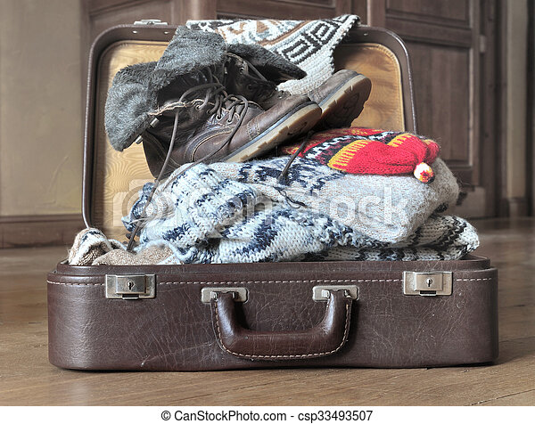 2e44670cb74 Warm cloths for winter. Open suitcase full of warm clothes on the floor.