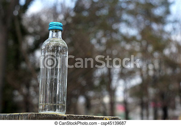 Water bottle on a background of blurred trees after sunset - csp45139687