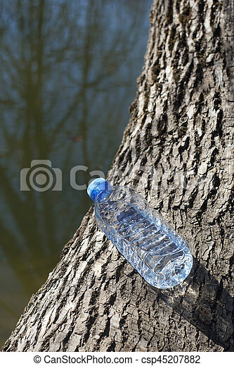 Water bottle on a background of tree bark - csp45207882