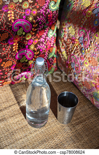 Water bottle on wood table with colorful pillow background in indian cafe - csp78008624