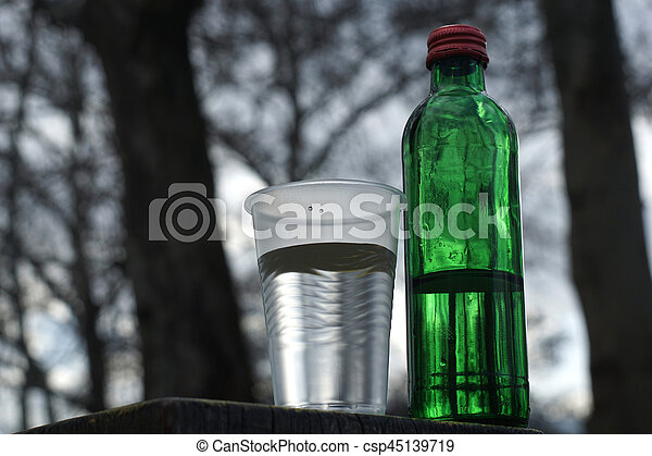 Water bottle with glass on a background of blurred trees - csp45139719