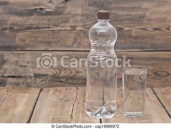 Water bottle with glass on wooden table - csp19966972