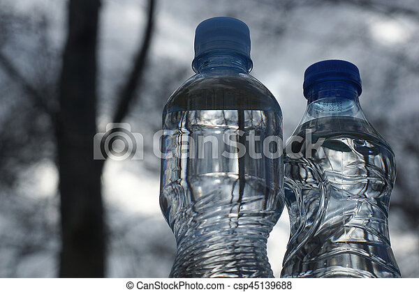 Water bottles on a background of blurred trees after sunset - csp45139688