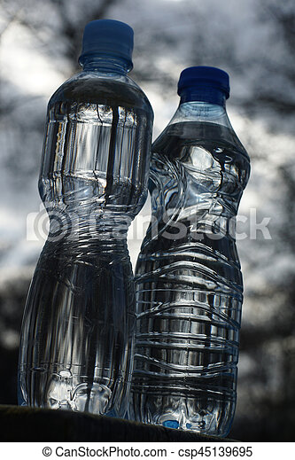 Water bottles on a background of blurred trees after sunset - csp45139695