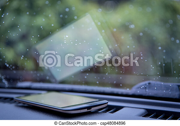 Water drops on car windshield with smartphone - csp48084896