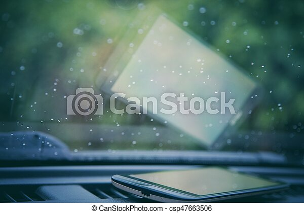 Water drops on car windshield with smartphone - csp47663506