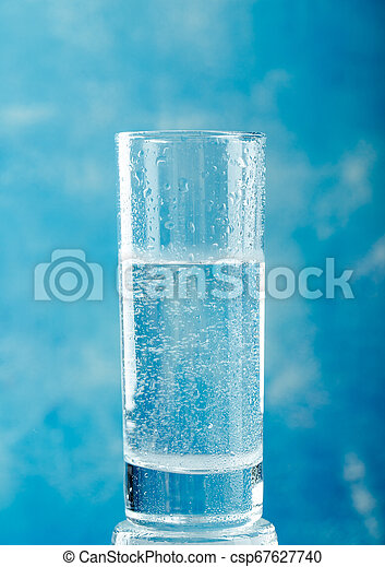 Water glass on blue background - csp67627740
