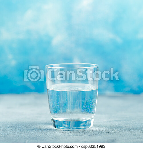 Water glass on blue background - csp68351993
