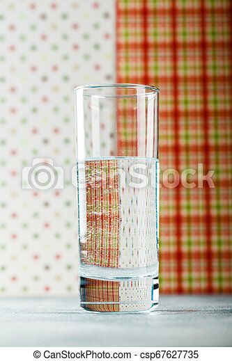 Water glass on blue background - csp67627735