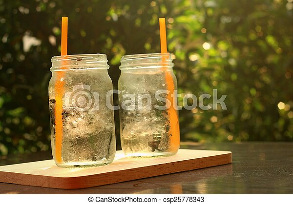 Water in a glass on a tray of wooden. - csp25778343