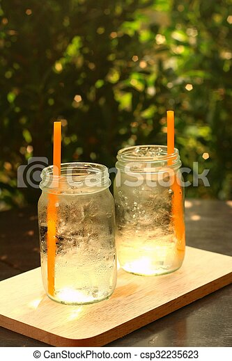 Water in a glass on a tray of wooden. - csp32235623