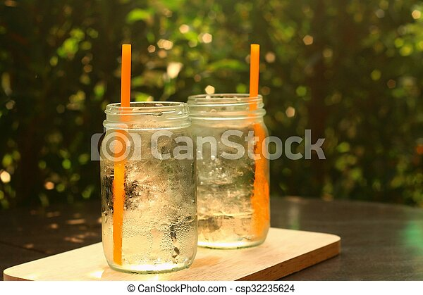 Water in a glass on a tray of wooden. - csp32235624