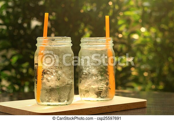Water in a glass on a tray of wooden. - csp25597691