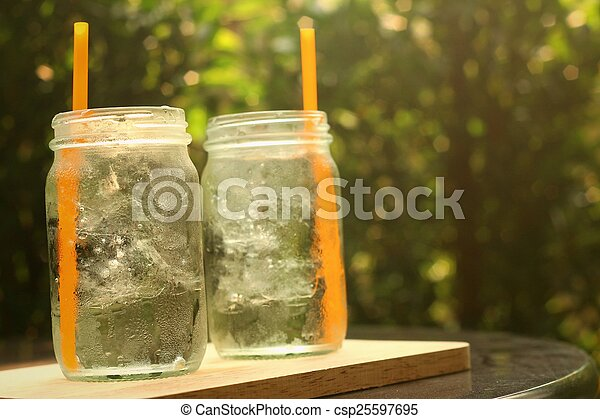 Water in a glass on a tray of wooden. - csp25597695