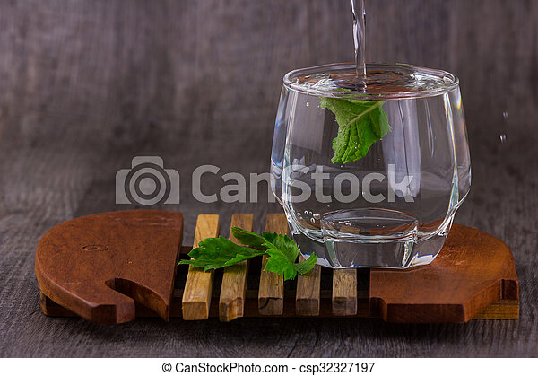 Water is poured into a glass - csp32327197