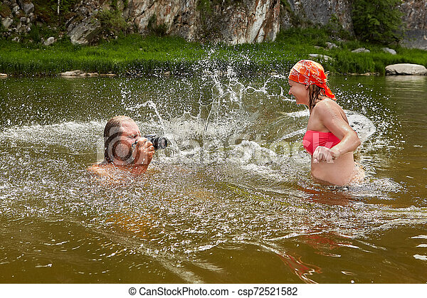 Water play by man and young woman. - csp72521582