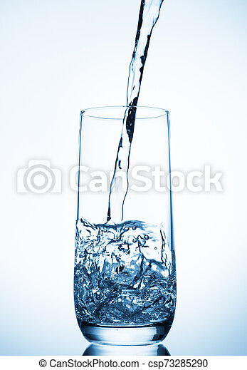 water pouring into glass on blue background - csp73285290