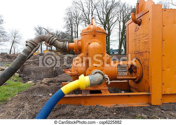 Water pumping station. Orange water pumping machine pumping away ground  water. | CanStock