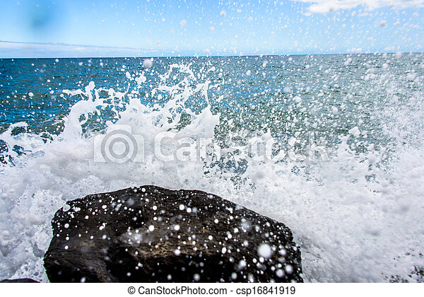 Water splashes on rock with the ocean in the background - csp16841919
