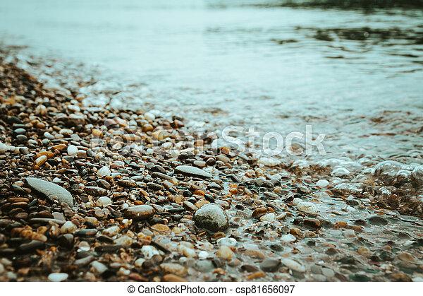Water worn pebbles at the edge of a lake - csp81656097