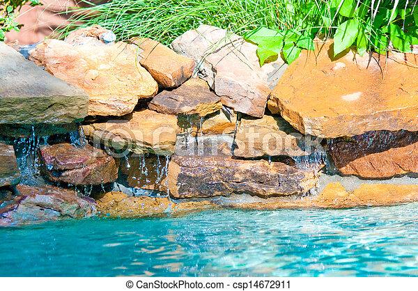 waterfall falling in a blue swimming pool