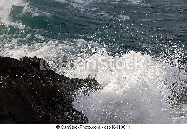 Waves crashing against rocks - csp16410611