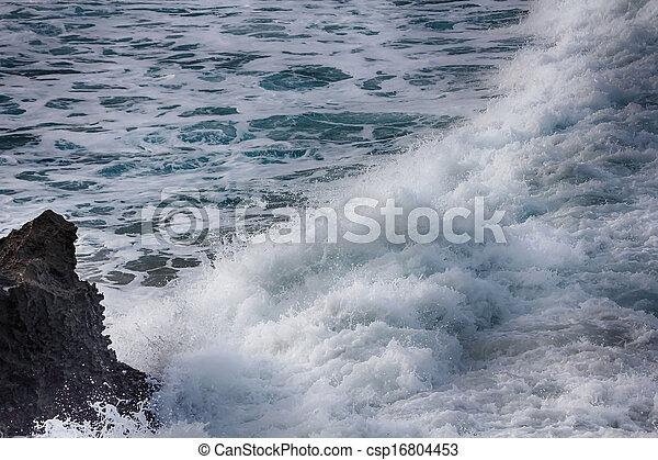 Waves crashing against rocks - csp16804453