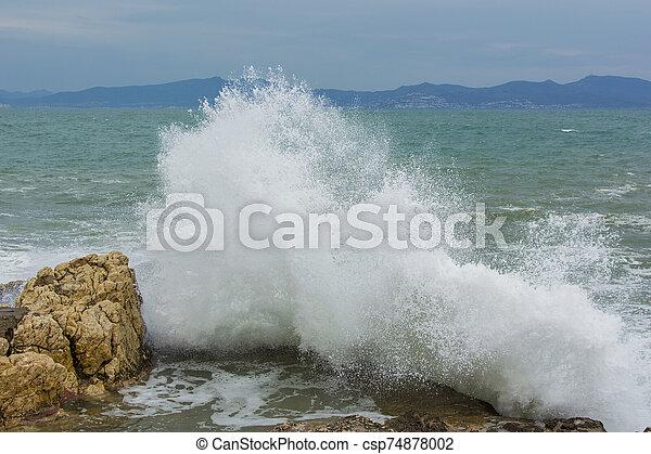 Waves crashing on rocks - csp74878002