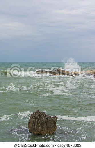 Waves crashing on rocks - csp74878003