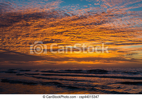 Waves in the Atlantic Ocean and sunrise, at Folly Beach, South Carolina. - csp44015347