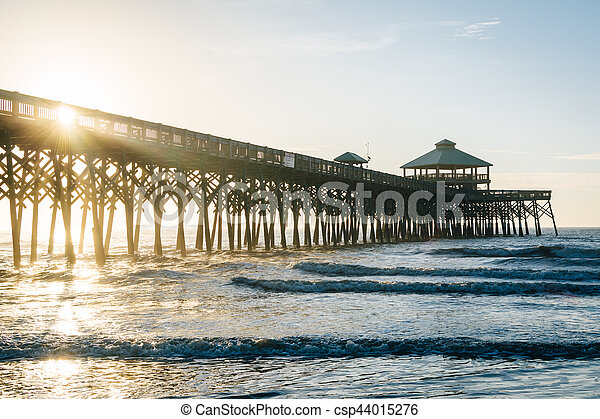 Waves in the Atlantic Ocean and the pier at sunrise, in Folly Beach, South Carolina. - csp44015276