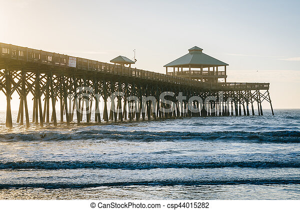 Waves in the Atlantic Ocean and the pier at sunrise, in Folly Beach, South Carolina. - csp44015282