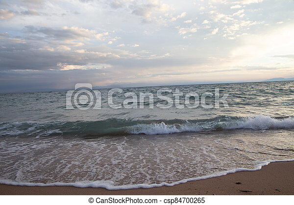 Waves in the rays of the setting sun. Natural landscape - csp84700265