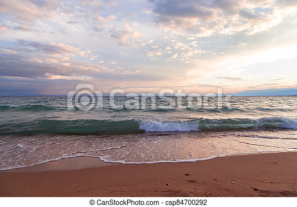 Waves in the rays of the setting sun. Natural landscape - csp84700292