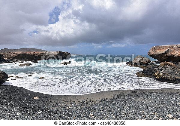 Waves Receding on the Black Pebble Beach in Aruba - csp46438358
