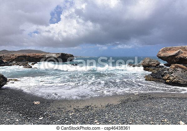 Waves Rolling Onto the Black Sand Stone Beach in Aruba - csp46438361